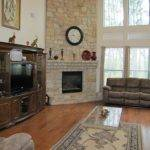 Living Room Offers Stunning Soaring Two Story Stone Fireplace