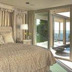 Opulent Bedroom Looks Out Over Small Pool Area Deck Beyond